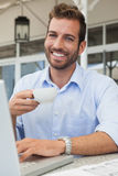 Happy young businessman working at laptop drinking coffee Stock Image