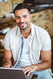 Happy young businessman working at laptop drinking coffee. At coffee shop Stock Photos