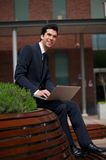 Happy young businessman working outdoors with laptop Stock Photo