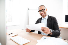 Happy young businessman working with papers in office Stock Photography