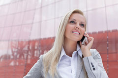 Happy young businesswoman communicating on smart phone against office building Stock Photo