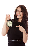 Happy young businesswoman holding alarm clock Stock Photo