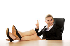 Happy young businesswoman holding legs on the desk Royalty Free Stock Photography