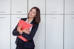 Happy young businesswoman holding a red binder And smiling. Happy young businesswoman holding a red binder Stock Photo