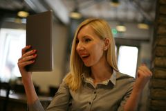 Happy young businesswoman with iPod. Young businesswoman on a break received good news on the tablet Stock Photography