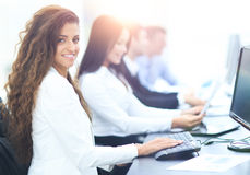 Happy young businesswoman looking behind and her colleagues work Royalty Free Stock Photo