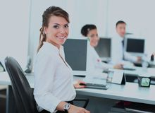 Happy young businesswoman looking behind and her colleagues working at office. Stock Photography