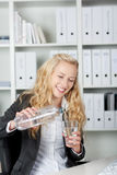 Happy Young Businesswoman Pouring Water In Glass Stock Photography