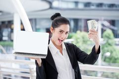 Happy young businesswoman is showing money and laptop with blank copy space screen and clipping path in urban city. girl holding. Cash of online business stock images