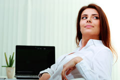 Happy young businesswoman sitting on her workplace and looking away Stock Photos