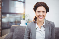 Happy young businesswoman sitting on sofa. Portrait of happy young businesswoman sitting on sofa in office Stock Photo