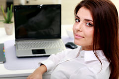 Happy young businesswoman sitting at the table on her workplace Stock Image