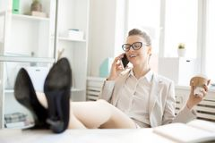 Relax in office. Happy young businesswoman with smartphone and glass of coffee relaxing by her workplace and calling Royalty Free Stock Photo