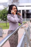Happy young businesswoman talking on cell phone. Outdoors Royalty Free Stock Photos