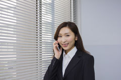 Happy young businesswoman talking with a mobile phone Stock Photography
