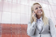 Happy young businesswoman using cell phone against office building Stock Photography