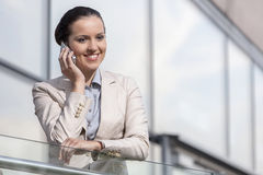 Happy young businesswoman using cell phone at office railing Royalty Free Stock Photography