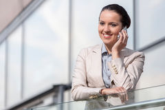 Happy young businesswoman using cell phone at office railing Royalty Free Stock Images