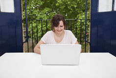 Happy young businesswoman using laptop at desk Stock Image