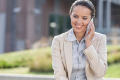 Happy young businesswoman using mobile phone while looking down outdoors Royalty Free Stock Images