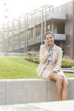 Happy young businesswoman using mobile phone while sitting on wall against office building Royalty Free Stock Photos
