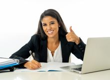 Happy young businesswoman working on her computer on her desk in satisfied at work and successful woman isolated on white. Background royalty free stock photo