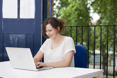 Happy young businesswoman working on laptop at desk Royalty Free Stock Images