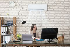 Businesswoman Working In Office With Air Conditioning. Happy Young Businesswoman Working In Office With Air Conditioning Stock Image
