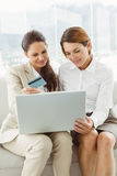 Happy young businesswomen doing online shopping Royalty Free Stock Photos