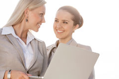 Happy young businesswomen with laptop looking at each other against sky Stock Image