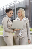 Happy young businesswomen with laptop standing against office building Royalty Free Stock Photo