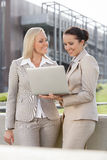 Happy young businesswomen with laptop standing against office building Royalty Free Stock Image