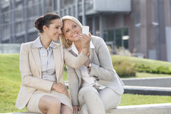 Happy young businesswomen taking self portrait through mobile phone against office building Royalty Free Stock Images