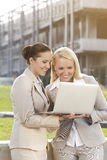 Happy young businesswomen using laptop together against building stock photos