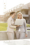 Happy young businesswomen using laptop together while standing against building Royalty Free Stock Image