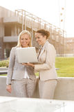 Happy young businesswomen using laptop together while standing against building Stock Images