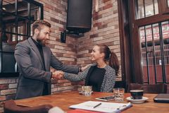 Businesswoman and businessman shaking hands stock images