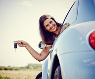 Happy Young car woman showing car keys. Woman driver Holding Her new Car keys out of the window, smiling looking into Camera Stock Image