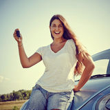 Happy Young car woman showing car keys. Woman driver Holding Her new Car keys, smiling looking into Camera Stock Photo