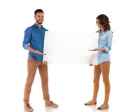 Happy young casual couple presenting big blank board. On white background Stock Image