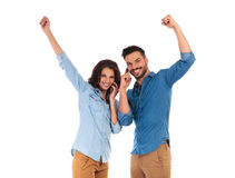 Happy young casual couple talking on phones celebrating success. Happy young casual couple talking on phones standing with hands in the air, celebrating success Stock Image