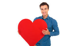Happy young casual man holding a big red heart Royalty Free Stock Photography