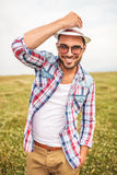 Happy young casual man holding his hat and smiles Stock Photo