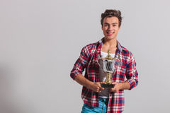 Happy young casual man holding a trophy cup. And smiles on grey background royalty free stock photography
