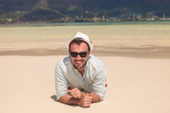 Happy young casual man lying on a white sand  beach. And smiles to the camera Stock Photography
