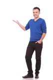 Happy young casual man presenting something. Full body picture of a happy young casual man presenting something Royalty Free Stock Photo