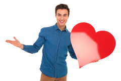 Happy young casual man welcoming you to valentine`s day Royalty Free Stock Images