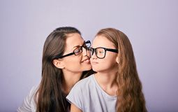 Happy young casual mother and smiling kid in fashion glasses hugging and looking each other on purple background with empty copy royalty free stock images