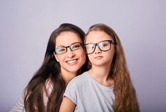 Happy young casual mother and smiling kid in fashion glasses hugging on purple background with empty copy space royalty free stock image