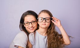 Happy young casual mother and smiling kid in fashion glasses hugging on purple background with empty copy space royalty free stock photo